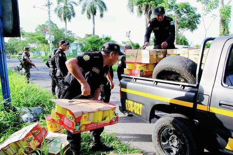 Agentes de la PNC y soldados suben a palangana de autopatrulla la mercadería decomisada en la ciudad de Retalhuleu. (Foto Prensa Libre: Rolando Miranda)