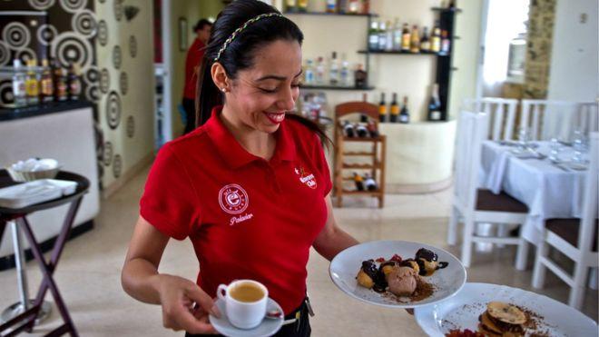 Una camarera soriente y vestida de rojo... propina a la vista