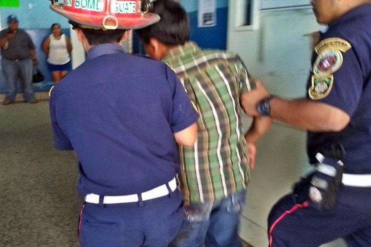 Socorristas atienden al pequeño comerciante que resultó con golpes, en Colomba. (Foto Prensa Libre: Alexánder Coyoy).