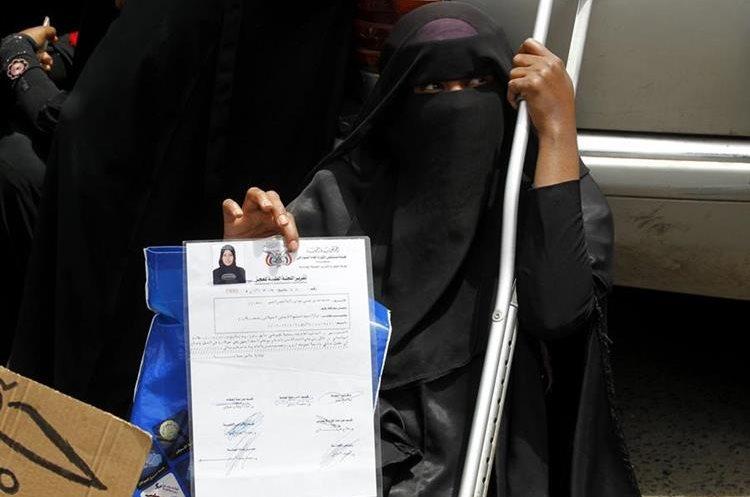 Una mujer de somalia muestra un informe médico durante una manifestación con motivo del Día Mundial de las Personas Refugiadas. (Foto Prensa Libre: EFE)