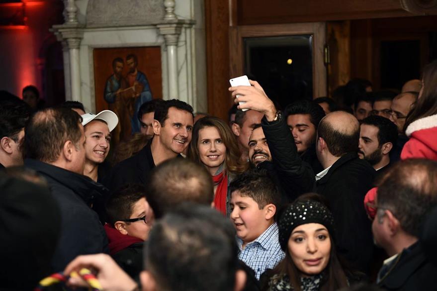 El presidente sirio, Bashar al Asad, se fotografía con simpatizantes en una iglesia de Damasco, a donde acudió para revisar los preparativos de Noche Buena. (Foto Prensa Libre: AFP).