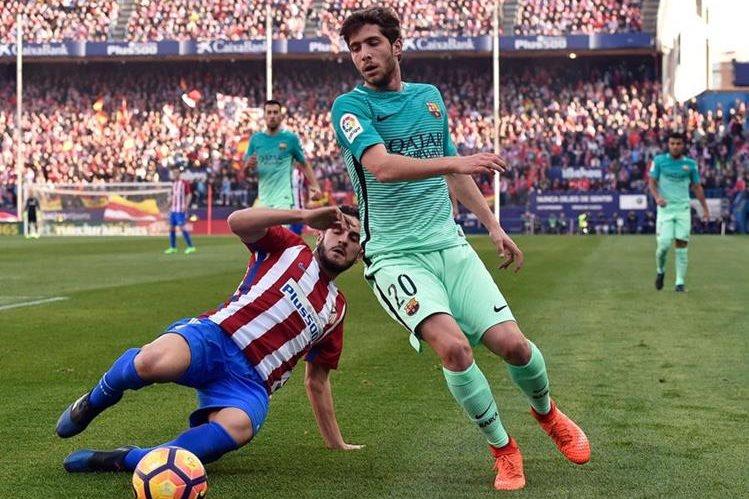 Koke y Sergi Roberto pelean por el balón en el partido disputado en el Vicente Calderón. (Foto Prensa Libre: AFP)