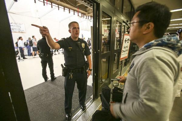 Un policía informa a un pasajero de la terminal 7 en el aeropuerto de Los Ángeles. (AP).