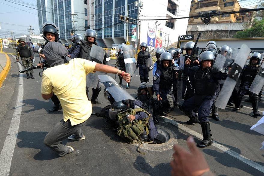 Un manifestante se enfrenta a personal antimotines en la capital hondureña. (Foto Prensa Libre: AFP).
