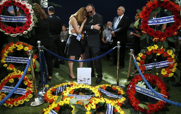 Dos personas lloran ante la tumba de Shimon Peres, durante el funeral de Estado. (EFE).