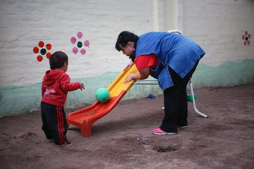 Garella juega con un alumno de preescolar en la escuela donde se desarrolla como profesional. (Foto Prensa Libre: AFP).