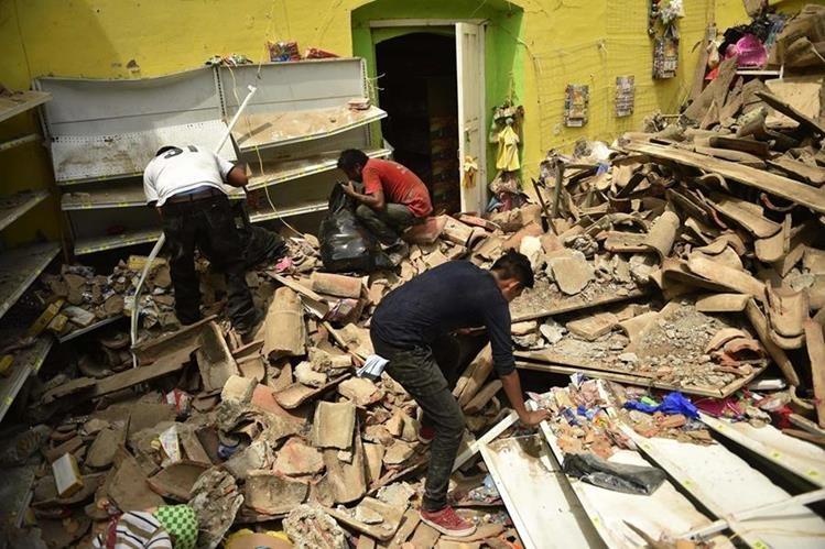 Pobladores tratan de rescatar algunas de sus pertenencias entre los escombros que dejó el terremoto en Juchitán de Zaragoza, Oaxaca, México. (Foto Prensa Libre: AFP).