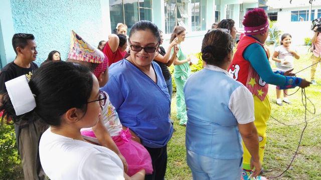Astrid observa junto a médicos cómo el payaso Mostacita manipula la piñata en la fiesta. (Foto Prensa Libre: Rony Pocon)