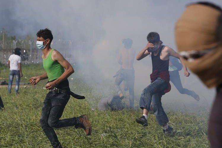 Migrantes se enfrentan a la Policía de Macedonia. (Foto Prensa Libre: AP).