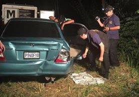 Autoridades del MP registran el vehículo en el que se hallaron los paquetes. (Foto Prensa Libre: Cortesía)