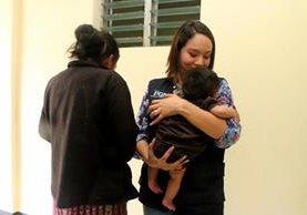 Trabajadora de la PGN sostiene al bebé, a la izquierda la madre de 17 años. (Foto Prensa Libre: Rolando Miranda)