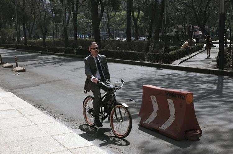 A man rides his bicycle along Reforma Avenue in Mexico City, Wednesday, April 6, 2016. City authorities have barred millions of vehicles from the streets due to a pollution alert. (AP Photo/Dario Lopez-Mills)
