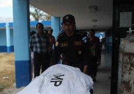 Agente de la PNC traslada el cadáver de Sherlyn Beraly Lajuj Ramos a la morgue de Huehuetenango. (Foto Prensa Libre: Mike Castillo).