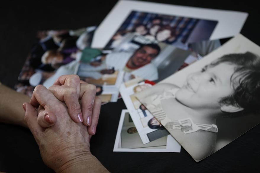 Lidia Guerrero muestra fotografías familiares de su hijo condenado a muerte. (Foto Prensa Libre: AP).