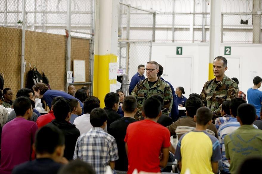 Unos menores escuchan orientaciones de dos agentes mientras esperan pasar un control medico al recién llegar a EE. UU. (Foto Prensa Libre: Hemeroteca PL).