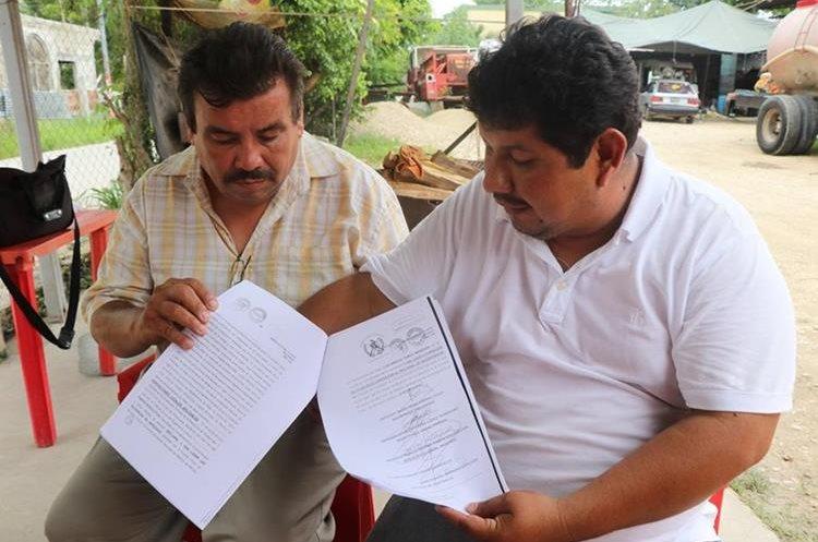 Juan Chavarría Cruz, secretario del sindicato de la comuna de Melchor de Mencos, y Jorge Salas Bolom, secretario de la gremial de Sindicatos Municipales de Petén, muestran la notificación donde se establece que el alcalde perdió su inmunidad. (Foto Prensa Libre: Rigoberto Escobar)
