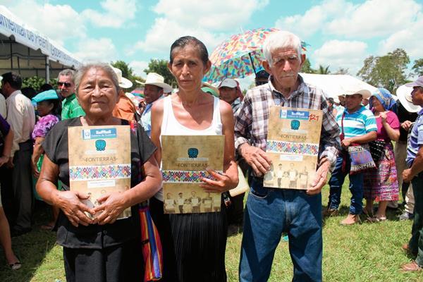 Tres de los beneficiados con escrituras de terrenos en Petén. (Foto Prensa Libre: Rigoberto Escobar)