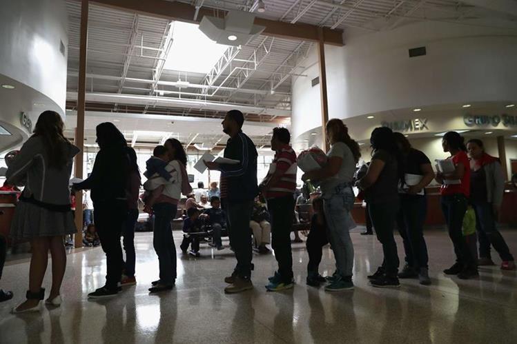 Familias de inmigrantes esperan a ser registrados en oficinas de inmigración de Macallen, Texas. (Foto Prensa Libre: AFP).