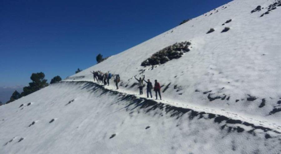 Los montañistas caminan entre los caminos llenos de nieve.