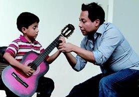 Dilan Gómez, de 7 años, atiende los consejos de Luis Juárez Quixtán, para tocar correctamente la guitarra. (Foto Prensa Libre: Edwin Castro).