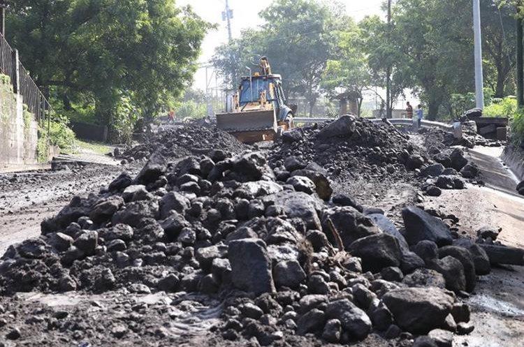 Maquinaria remueve el flujo que arrojó el volcán el lunes sobre la Ruta Nacional 14. (Foto Prensa Libre: Carlos Paredes)