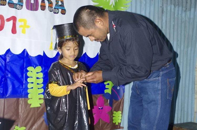 Un padre coloca el anillo de graduación a su hija. (Foto Prensa Libre: Eduardo Sam)