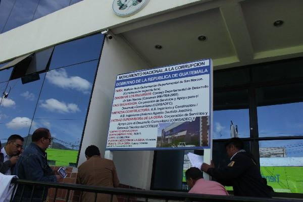 """El rótulo   frente a la Gobernación de San Marcos, que  lo nombra como """"monumento a la corrupción""""."""