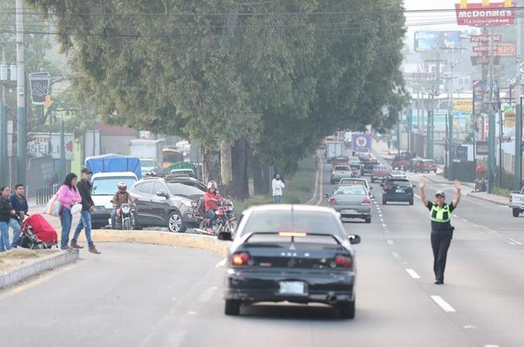 Una agente de la PMT coordina la incorporación de vehículos de la ruta Interamericana hacia zonas comerciales y residenciales de San Lucas Sacatepéquez. (Foto Prensa Libre: César Pérez)