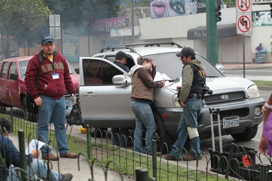Fiscales de la Dirección de Investigaciones Criminalísticas recogen evidencia en carro abandonado por supuestos secuestradores (Foto Prensa Libre: PNC)