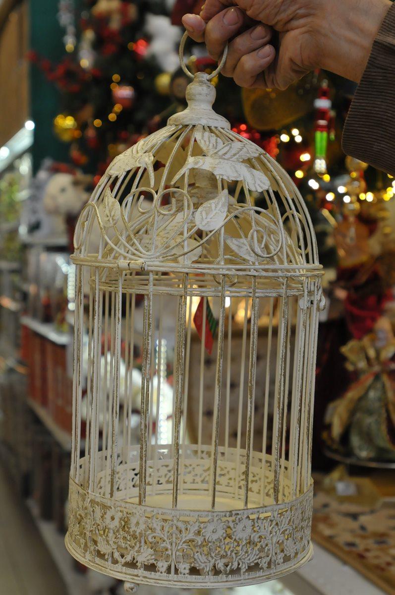 El estilo shabby-chic hace su entrada con objetos antiguos que renacen. A esta jaula, elemento no navideño, se le pueden colocar adentro esferas o estrellas brillantes.