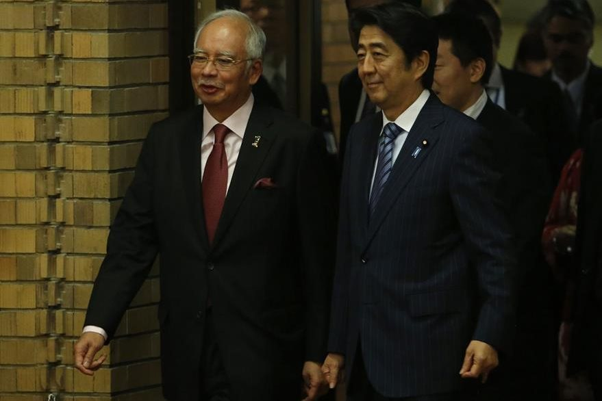 El primer ministro de Japón, Shinzo Abe (Derecha), impulsa una ley para que los trabajadores no cobren horas extras por permanecer más tiempo en el trabajo. (Foto Prensa Libre: AFP).