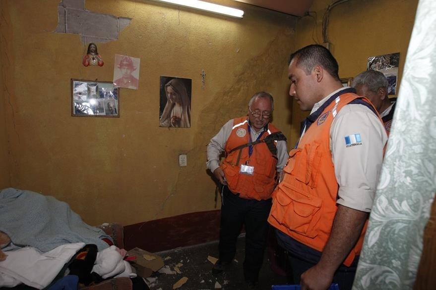Personal de Conred supervisan una vivienda en la que se formó una grieta. (Foto Prensa Libre: Paulo Raquec)