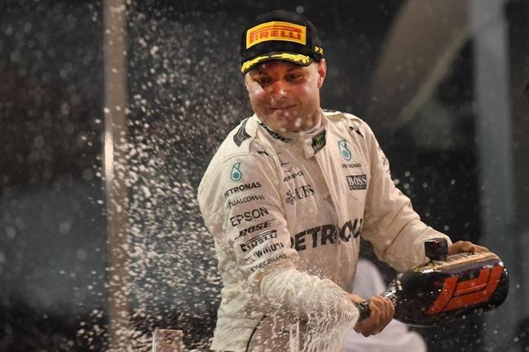 Valtteri Bottas celebra en el podio con el tradicional baño de champán. (Foto Prensa Libre: AFP)