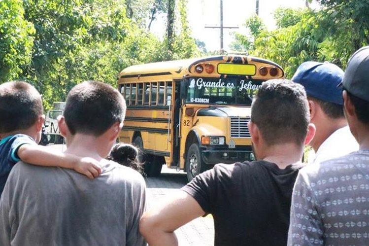 Vecinos observan el bus donde quedó el cadáver del piloto. (Foto Prensa Libre: Cristian Soto)