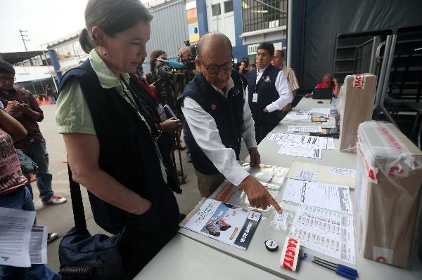 Un funcionario conversa con una observadora durante el traslado de material electoral.(EFE).