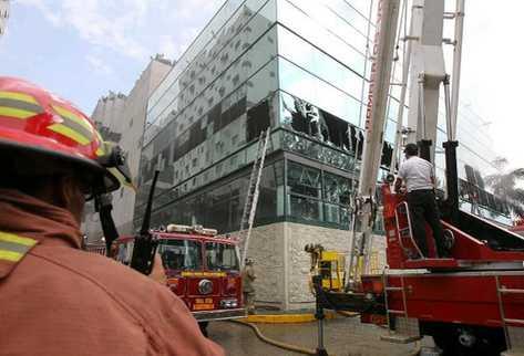 Bomberos rompen vidrios para sofocar las llamas. (Foto Prensa Libre: Alvaro Interiano)