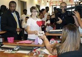 Leo Ellis,(c) entrega una tarjeta con un mensaje a una ayuda del alcalde Carlos Gimenez. (AP).