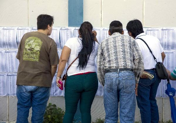Nicaragüenses buscan sus nombres en la lista del padrón electoral en Managua. (EFE).