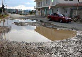 El agua de lluvia se reposa en los agujeros de gran tamaño, en Olintepeque, Quetzaltenango. (Foto Prensa Libre: Carlos Ventura)