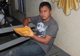 Uno de los presuntos secuestradores es trasladado hacia una subestación de la PNC en Lívingston. (Foto Prensa Libre: Edwin Perdomo)