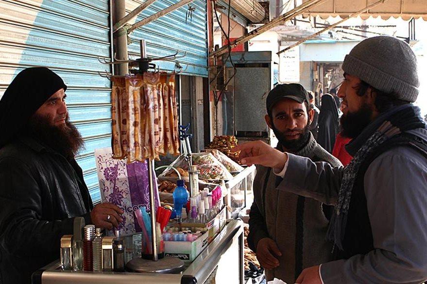 Un miembro del EI (derecha), platica con un vendedor de perfumes (izquierda), en una de las calles de Raqa en Siria. (Foto Prensa Libre: AP).