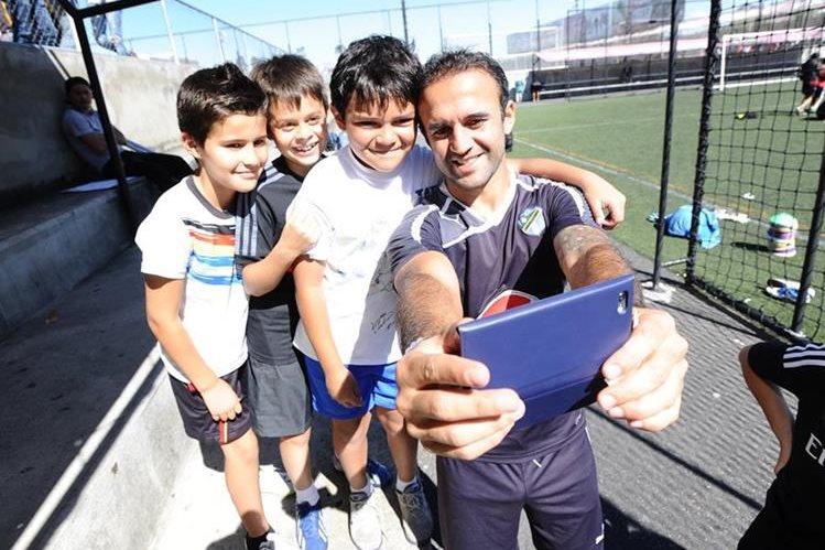 El volante de Comunicaciones José Contreras se toma una fotografía con su celuar acompañado de varios niños. (Foto Prensa Libre: Francisco Sánchez)
