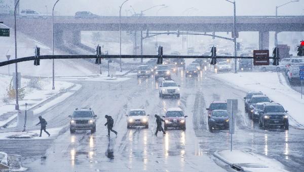 Los peatones cruzan Woodmen Road entre la nieve y fuertes vientos en Colorado EE.UU.