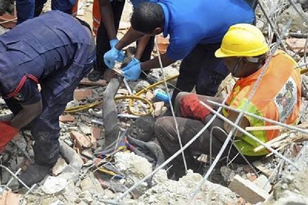 Rescatista asisten a un hombre atrapado entre los escombros.