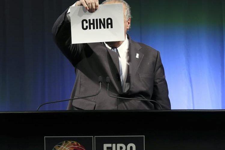 Horacio Muratore, presidente de FIBA sostiene el cartel con el nombre de la sede del mundial de 2019. (Foto Prensa Libre: AP)
