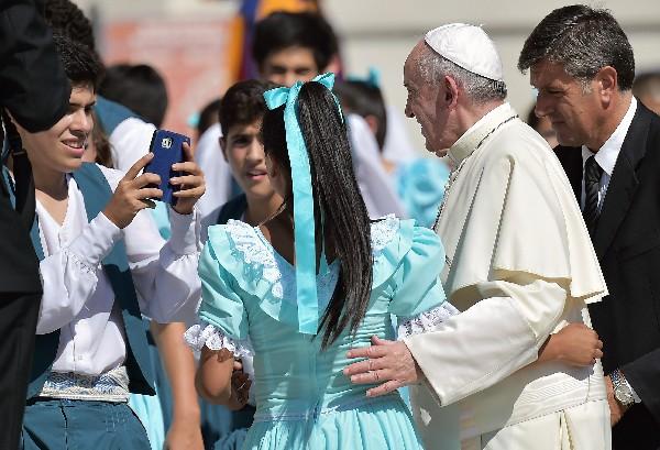 El Papa posa para fotos con varias niñas.