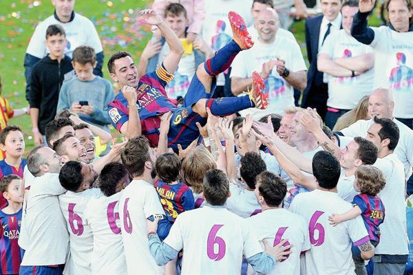 Xavi Hernández es levantado en hombros por sus compañeros quienes visten camisolas en homenaje. (Foto Prensa Libre: EFE)