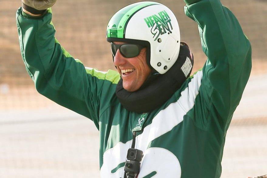 Luke Aikins alza las manos en señal de victoria luego de haber saltado sin paracaídas desde siete mil metros de altura y caer en una red. (Foto Prensa Libre: EFE).