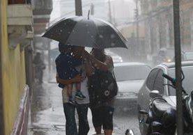 Guatemaltecos se cubren de la lluvia en la ciudad capital. (Foto Prensa Libre: Hemeroteca PL)
