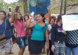 Un grupo de mujeres, con celulares en mano, protesta en tres colonias de Santa Elena por la falta de señal de telefonía. (Foto Prensa Libre: Rigoberto Escobar)